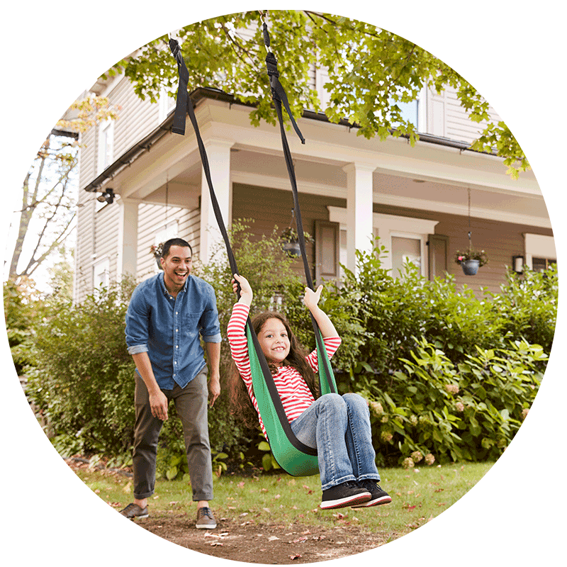 Father pushing his daughter on a swing in front of their new house after a home inspection