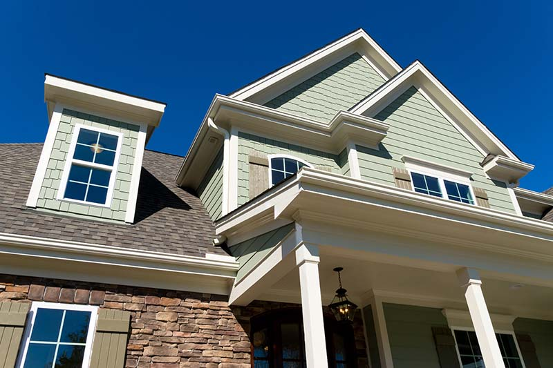 Looking up at the exterior of a house while providing home inspection services