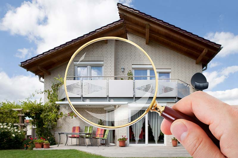 Hand holding a magnifying glass in front of a house while home inspection services are being preformed