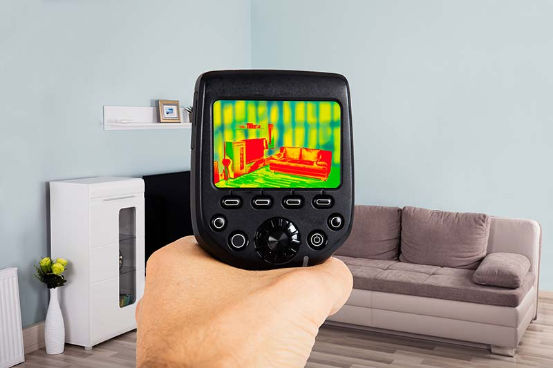 The hand of one of our home inspectors using a thermal imaging camera in a living room.